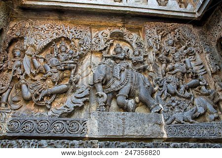Ornate wall panel reliefs depicting from left Garuda carrying Vishnu, Lord Indra and Indrani on elephant Eirawat and Vishnu rescuing Gajendra from crocodile, Hoysaleshwara temple, Halebidu, Karnataka, India. poster
