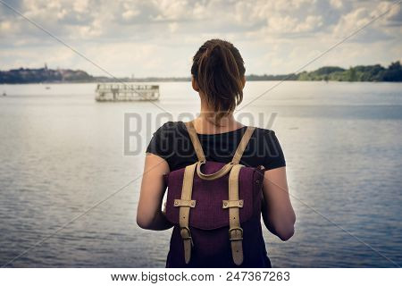 Traveler Girl Looking To River. Young Girl With Backpack Looking For A Boat. Girl Traveler Looking.