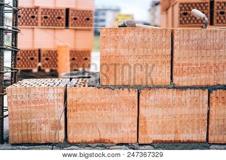 construction site of new building, details of brickwork and reinforcements with steel bars and wire rod poster