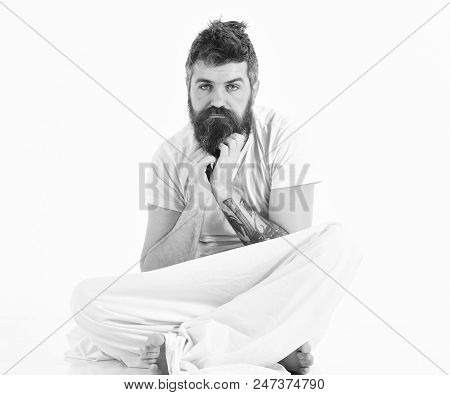 Hangover morning concept. Man with pensive face wake up, sits, scratching beard with hands. Man tired, having rest, white background. Hipster with beard, mustache and messy hair itching. poster