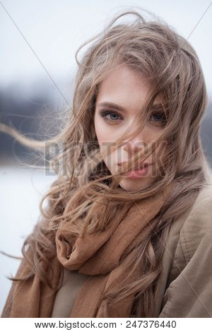 Beautiful Young Woman With Blowing Hair In Windy Day Outdoors