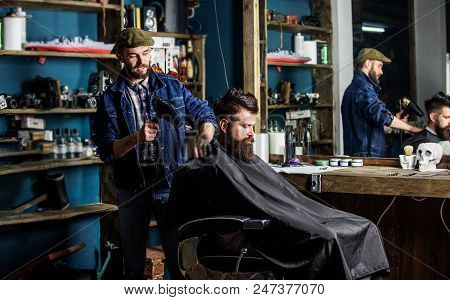 Barber with hairdryer works on hairstyle for bearded man barbershop background. Barber with hairdryer drying hair of client. Hipster lifestyle concept. Hipster bearded client getting hairstyle. poster