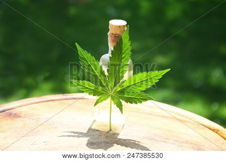 Hemp oil liquid in sun lighting with marijuana pal typical cannabis leaf poster
