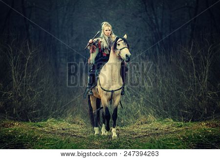 Warrior Woman On A Horse In The Woods. Beautiful Scandinavian Viking Riding Horse With Ax In Hand, B