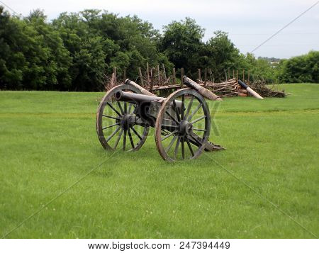 A Civil War Cannon With A Log Wall In The Background