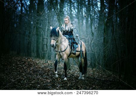 Warrior Woman On A Horse In The Woods. Scandinavian Viking Riding Horse With Ax In Hand, Blonde Hair