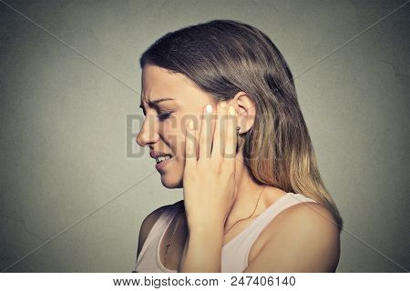 Tinnitus. Closeup Side Profile Sick Young Woman Having Ear Pain Touching Her Painful Head Isolated O