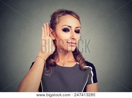 Pretty Young Model Holding Hand Near Ear And Listening With Concentration To Hearsays On Gray