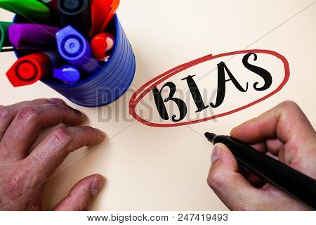 Conceptual hand writing showing Bias. Business photo text Unfair Subjective One-sidedness Preconception Inequality Bigotry Man holding black marker markers table ideas message communicate poster