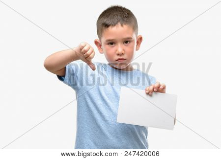 Dark haired little child holding a blank card with angry face, negative sign showing dislike with thumbs down, rejection concept poster