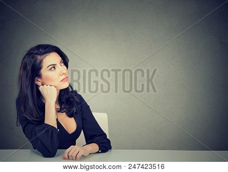 Thinking Young Business Woman Sitting At Desk Contemplating