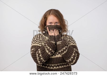 Woman In Warm Brown Sweater Hiding Her Face. Only Eyes Are Seen. She Wants To Stay Anonym. Fear Of P