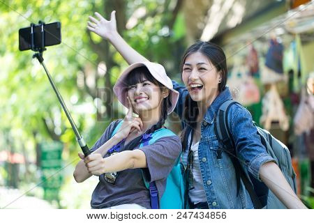 Portrait Of Happy Traveler Woman Selfie With Friend Together In City. Asian Women Using Smartphone W