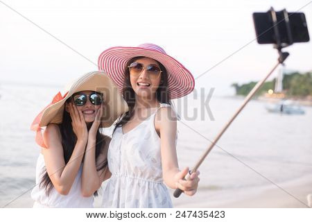 Portrait Of Happy Traveler Woman Selfie With Friend Together At Beach. Asian Women Using Smartphone