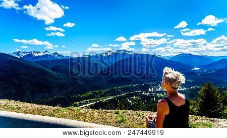Senior Woman Enjoying The View Of The Rugged Peaks Of The Cascade Mountain Range On The Us-canada Bo