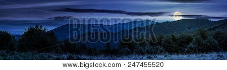 Panorama Of Carpathian Mountains At Night In Full Moon Light. Beautiful Landscape With Forested Hill