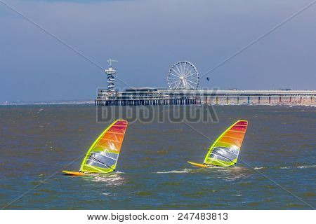 Scheveningen, The Hague, The Netherlands - June 27 2018: Speeding Windsurfers Sailing Off The Beach