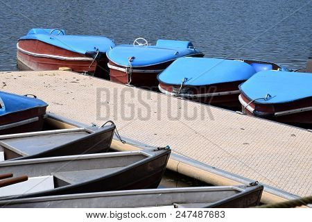 Old And Nostalgic Pedal Boats And Row Boats On A Pier, Row Boat And Pedal Boat Parked In A Line At T