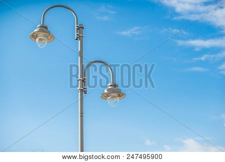 A Typical Double Lamppost On A Blue Sky Background.