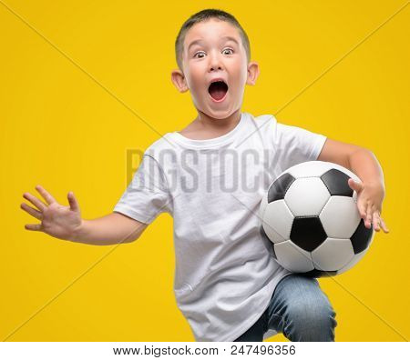 Dark haired little child playing with soccer ball very happy and excited, winner expression celebrating victory screaming with big smile and raised hands