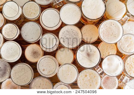 An Assortment Of Full, Frothy Beer Glasses And Sizes On A Bar Bench Top.