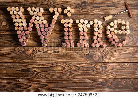 Word Wine Formed Of Used Red And White Wine Bottle Corks In Graduated Colors On A Rustic Wooden Back