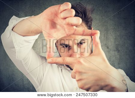 Young Man Making A Frame With Fingers Hands And Looking Through Limits At Camera On Gray Background