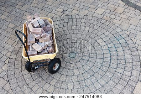 Trolley With Grey Pavers Or Bricks On A Paved Patio With Ornamental Circular Pattern Viewed High Ang