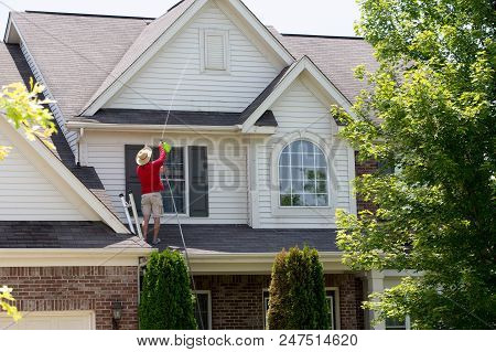 Man Cleaning The Upper Floor Exterior Of His Home Standing On The Lower Roof Using A Pressure Spraye