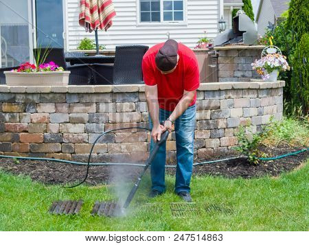Man Pressure Cleaning Dirty Grill Plates From A Bbq Using A Hosepipe And Nozzle As He Stands On The