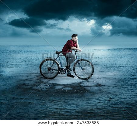 Young Man On A Bike Standing On A Piece Of A Road  In The Middle Of The  Ocean .