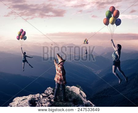 Young Man Up On Top Of A Mountain Point Out To People Flying With Balloons High Above The Mountains.