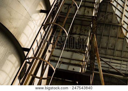Rusty Metal Ladder Attached To An Abandoned Industrial Building