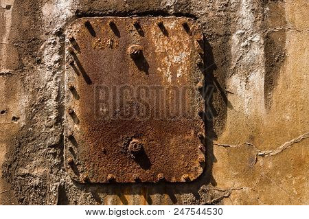 Rusty Old Metal Plate With Screws And Bolts On A Weathered Wall