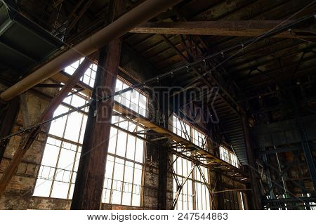 Interior Of An Abandoned Industrial Building With Large Glass Windows