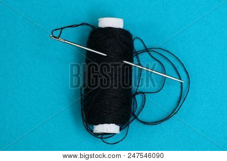 A Needle And Thread In A Reel With Black Threads On A Blue Table