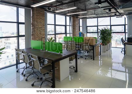 Empty Room With Tables In Modern Office. Open Space In Loft Style Office Building. Interior Concept
