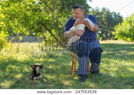 Nice Outdoor Portrait Of Senior Man His Cute Puppy Sitting Next To Him And White Goose On The Hands