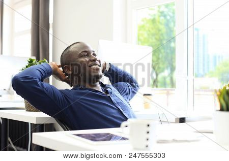 Relaxed Afro American Business Man Sitting At His Desk Looking Into The Air
