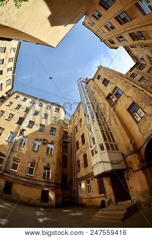 Bottom View Of Amazing Old Urban House Courtyard With Bird In The Blue Sky. Fish Eye Lens Effect.