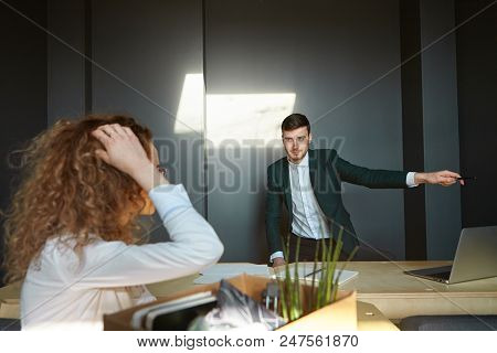 You're Fired. Serious Brunette Young Male Employer In Suit Pointing At Door While Firing Female Empl