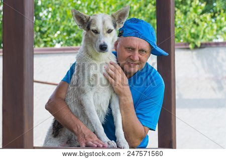 Nice Outdoor Portrait Of Happy Mature Man And His Cute Young Dog