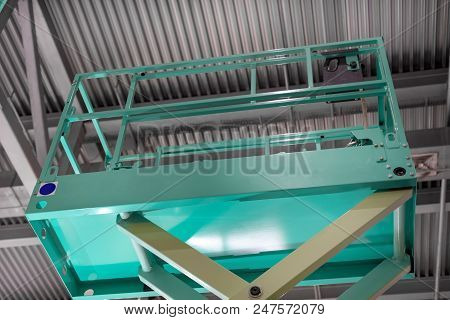 Hydraulic Scissor Lift Platform. The Platform Of The Lift Is Raised Under The Roof Of The Building.
