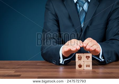 Insurance Concept. Businessman With Protective Gesture And Insurance Icons On Wooden Cubes: Family A