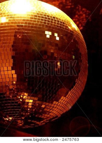 Shiny disco ball in motion reflecting golden light poster