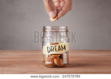 Dream. Glass Jar With Coins And An Inscription Dream. Man Holds  Coin In His Hand.