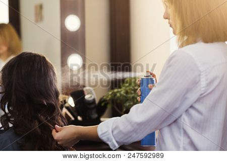 Stylist with hair spray making curly hairdo at beauty salon poster