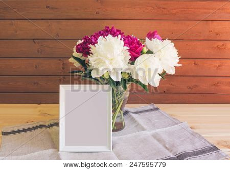 Red  And White Peonies In Vase And White Frame On Wooden Background