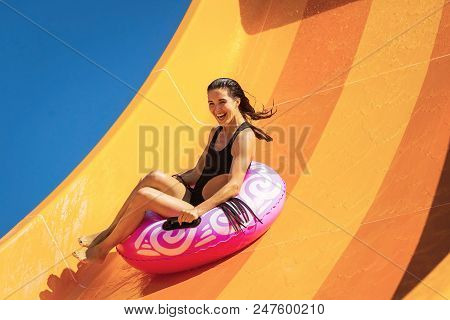 Young Pretty Woman On The Inflatable Ring Having Fun On The Orange Water Slide In The Aqua Park. Sum