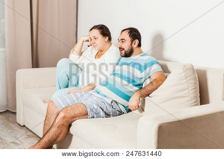 Couple At Home Relaxing In Sofa. Young Man And Woman Watching Tv.